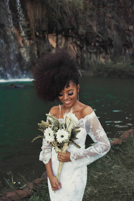 Woman standing near water holding bouquet