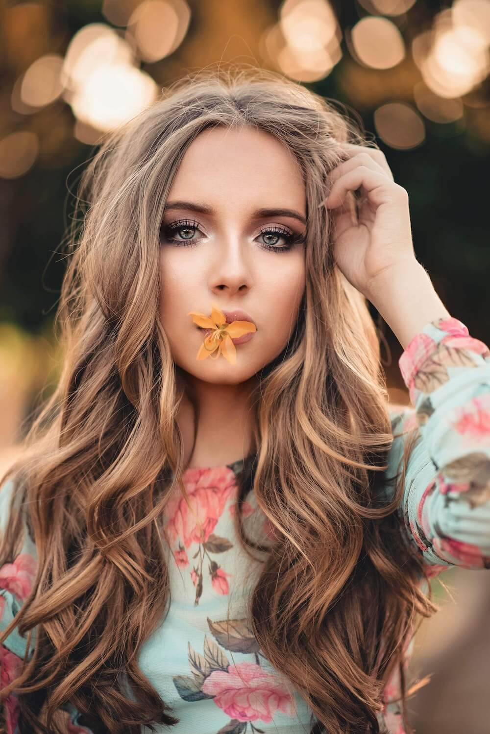 Woman with orange flower on her lips