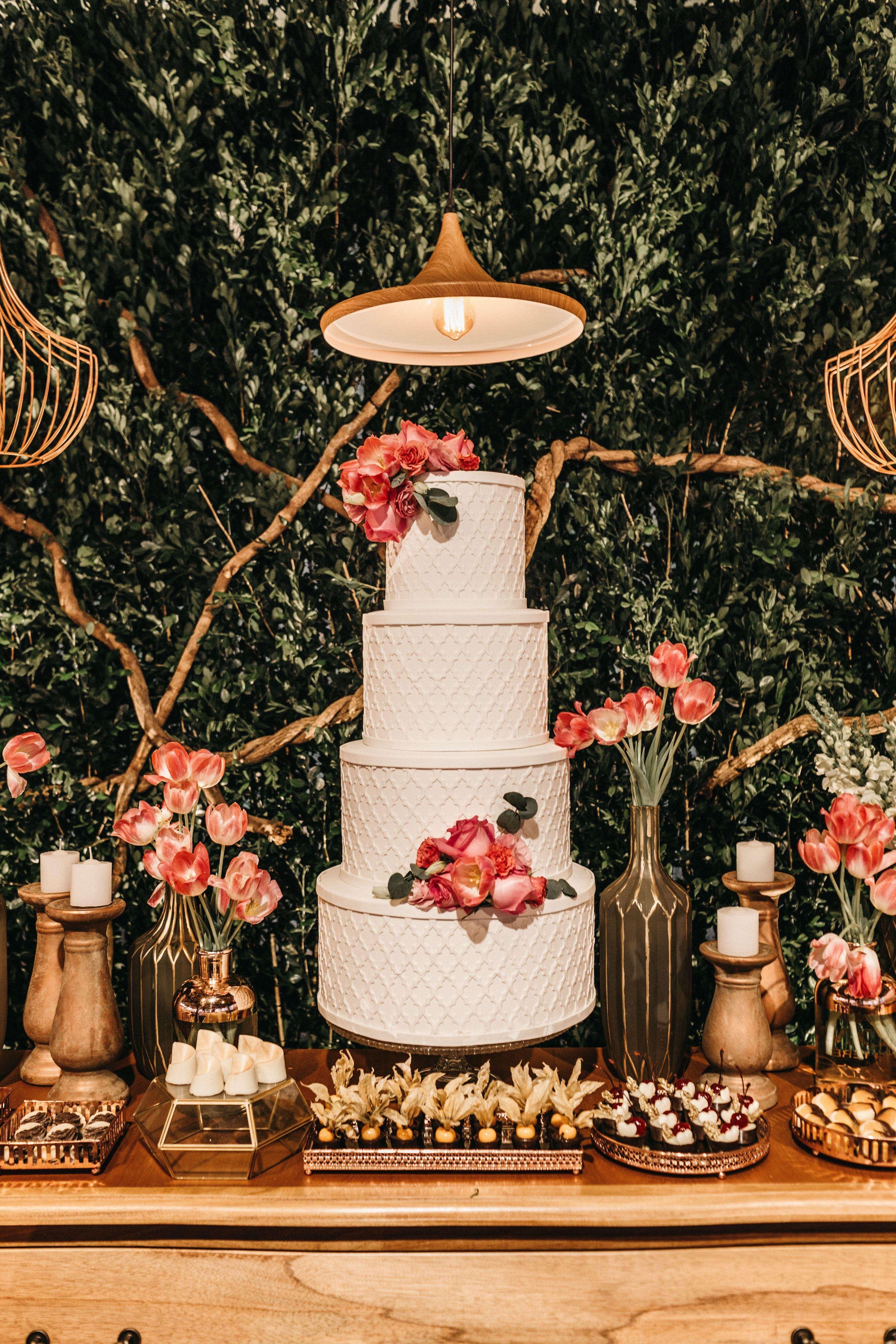 White four tier wedding cake on a dessert table