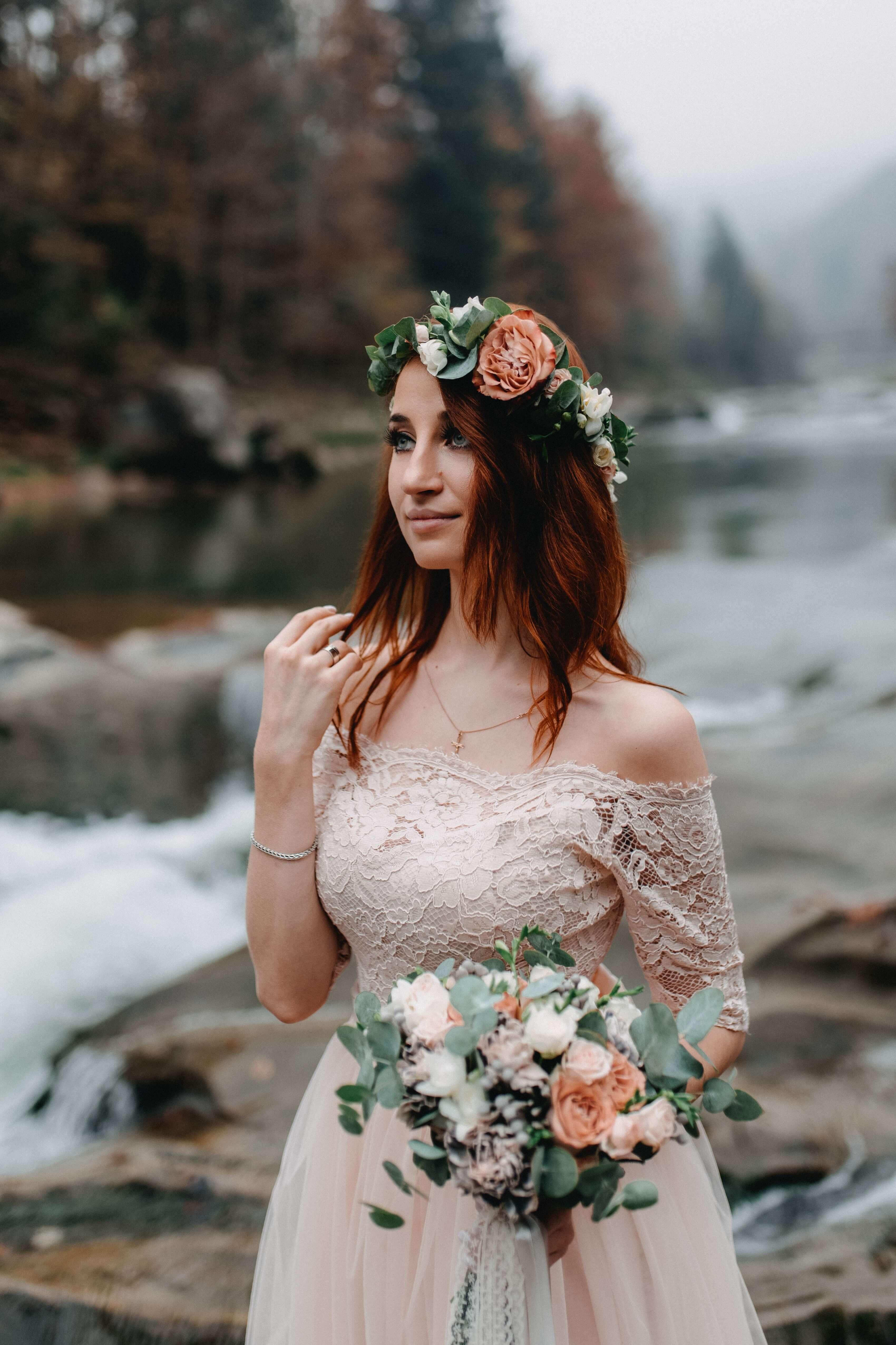 Woman wearing blush wedding dress and flower crown near riverl