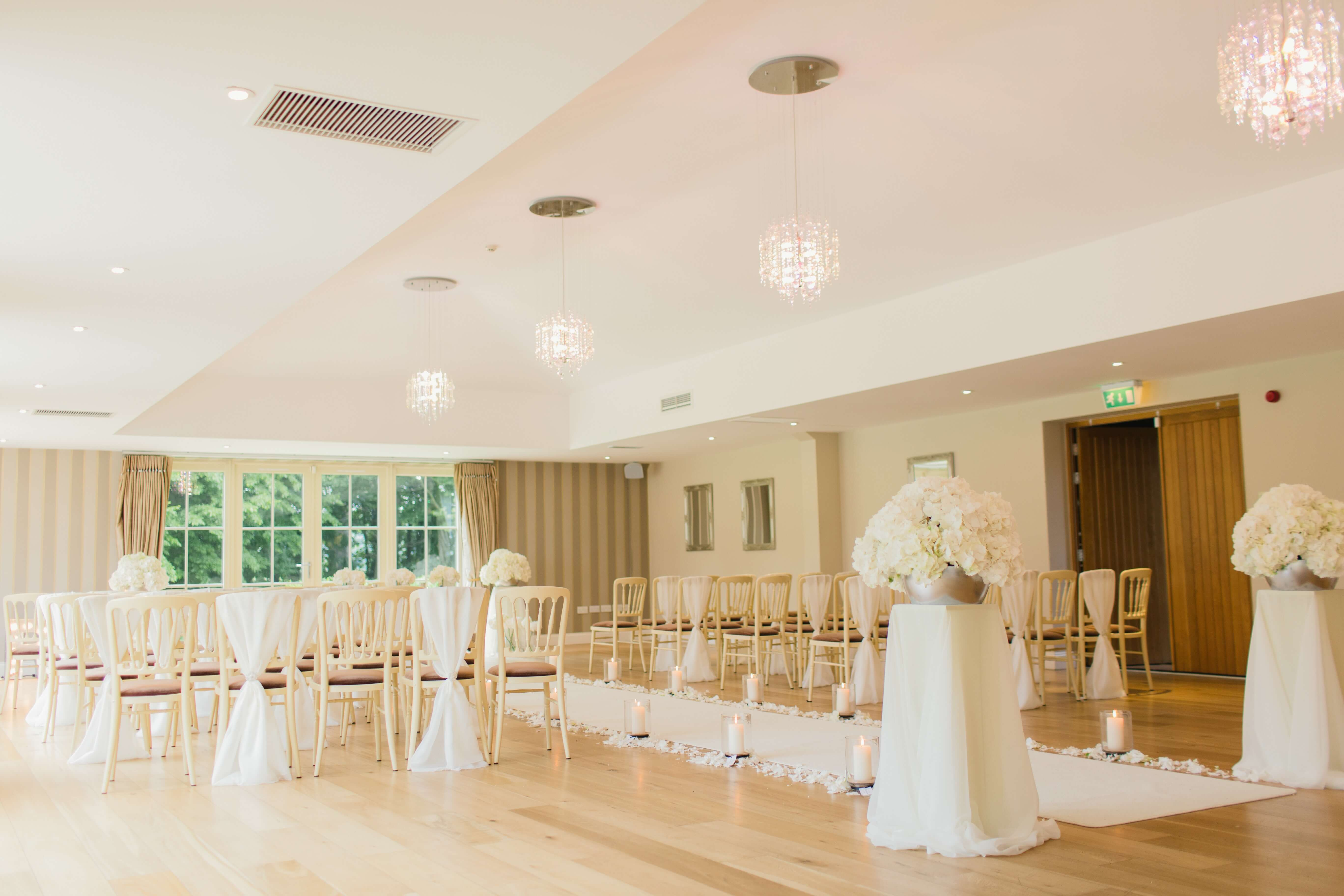 Dining hall set up for white wedding ceremony