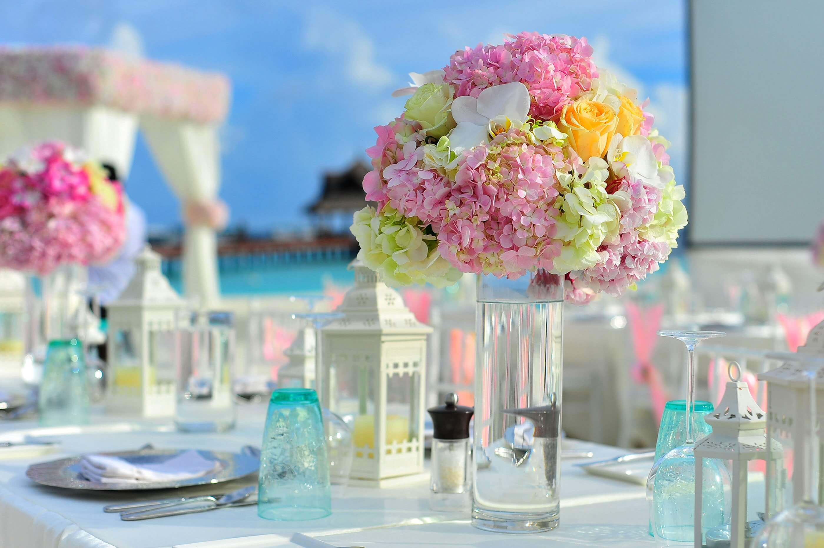 Wedding tables with colourful flower arrangement near ocean