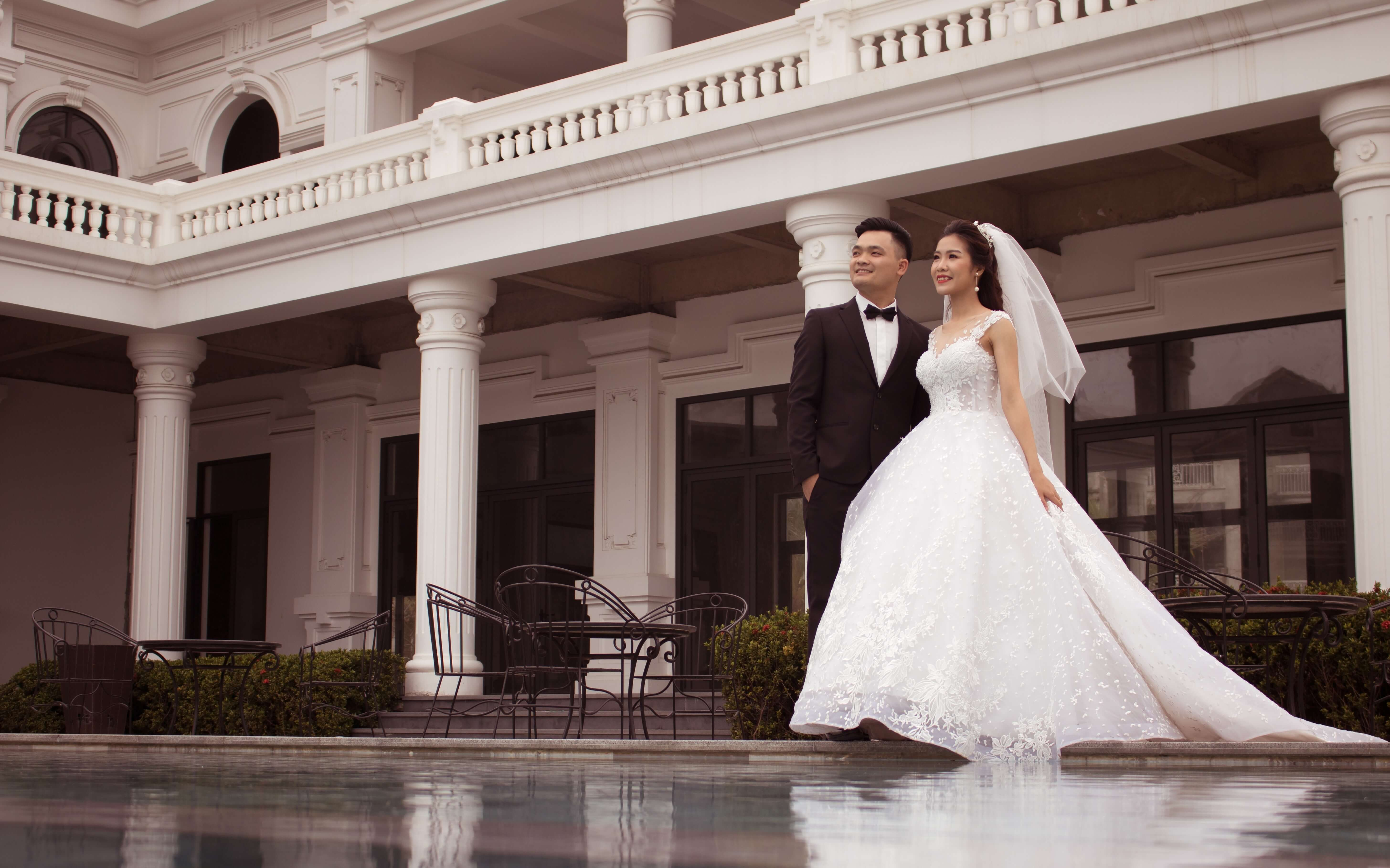 Bride and groom standing in a courtyard near a pool