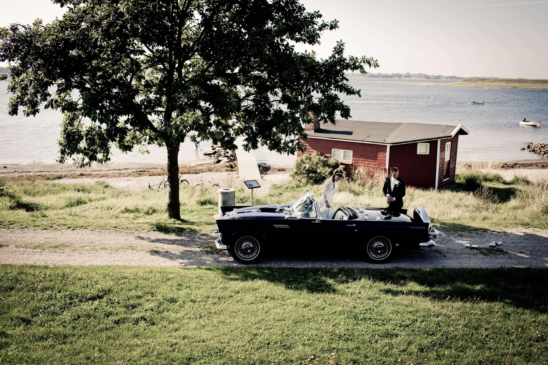 Bride and room standing near black vintage car