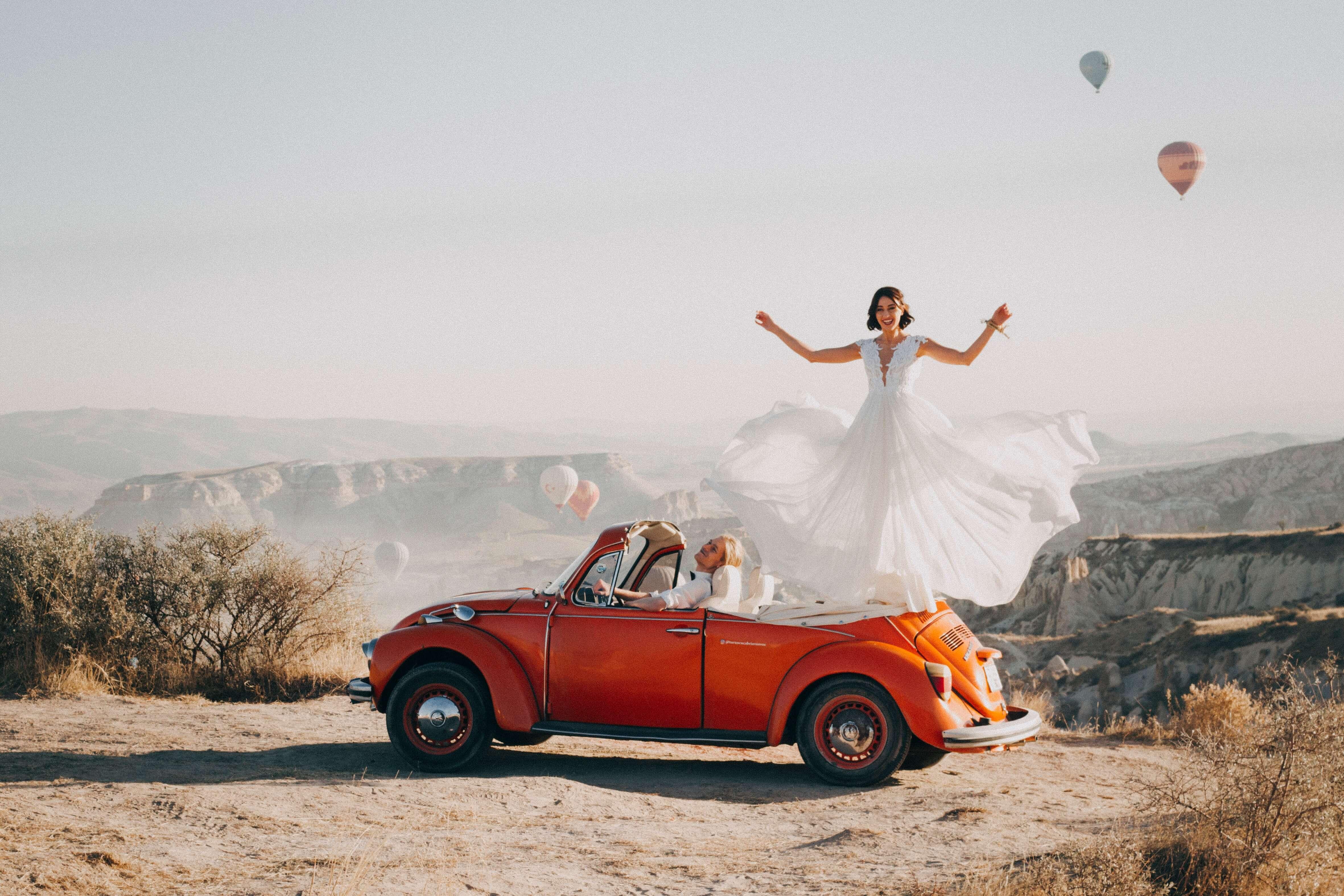 Woman wearing wedding dress standing on VW Beetle near canyon
