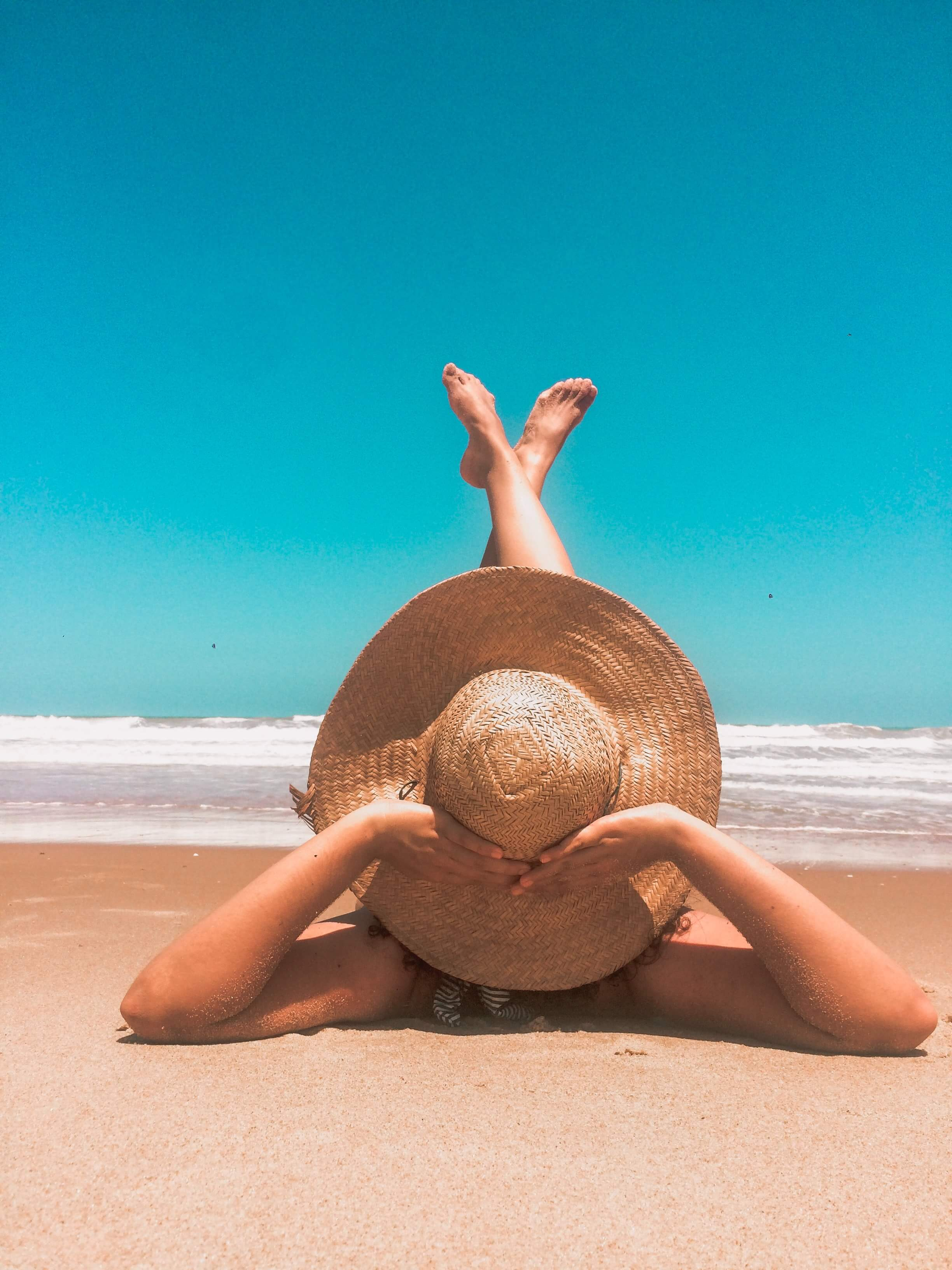 Person lying on sand with large sunhat