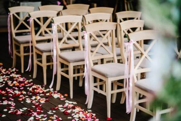 Wedding ceremony setup with ribbons on chairs and petals on the ground