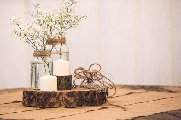 Table setting with delicate flowers in a jar, candles on a tree stump