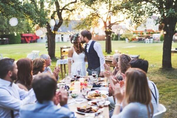 Bride & Groom kissing at the head of a picnic table