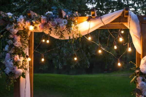 Wooden wedding arch draped in white sheet and fairy lights