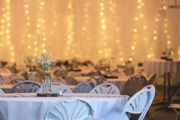 Dining hall with dressed tables and fairy lights in background