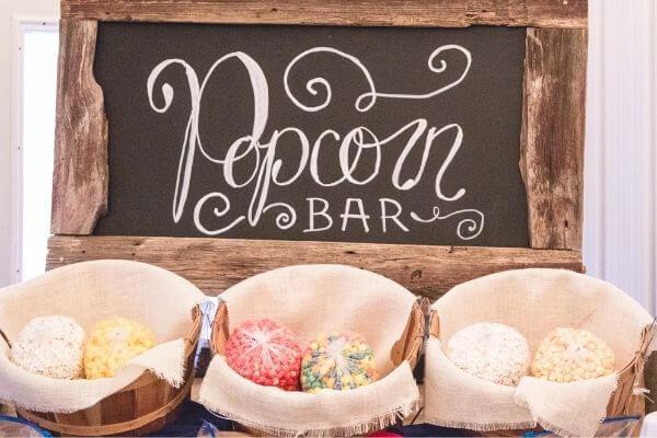 Chalkboard reading: Popcorn Bar with buckets of popcorn beneath