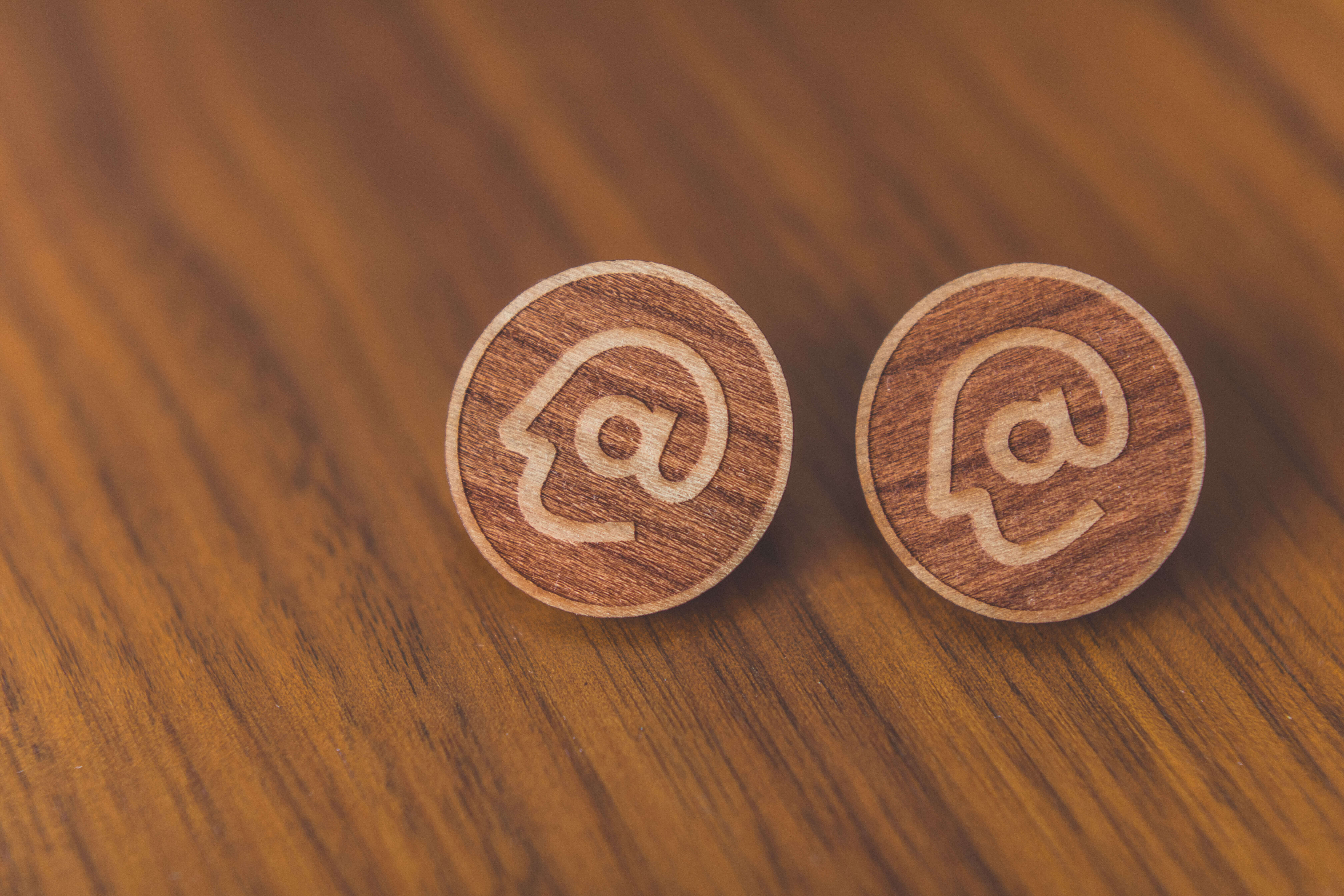 Close-up of two wood pins etched with Acumen's logo, designed by Serve.