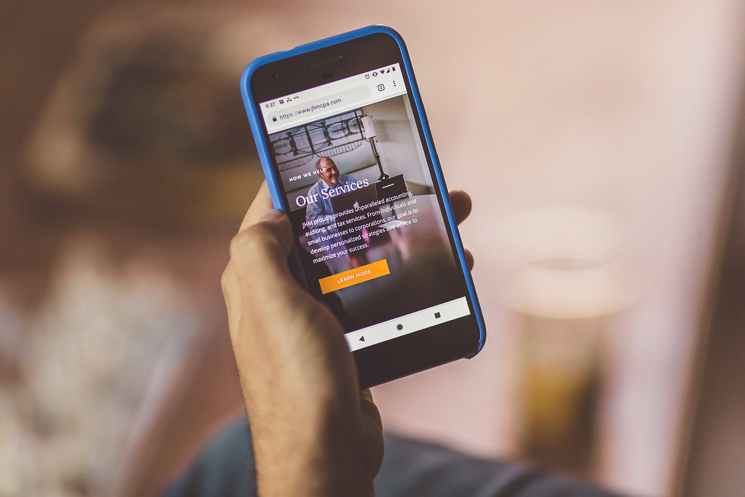 Over the shoulder shot of a mobile phone displaying the JHM site developed for Counsel Creative.