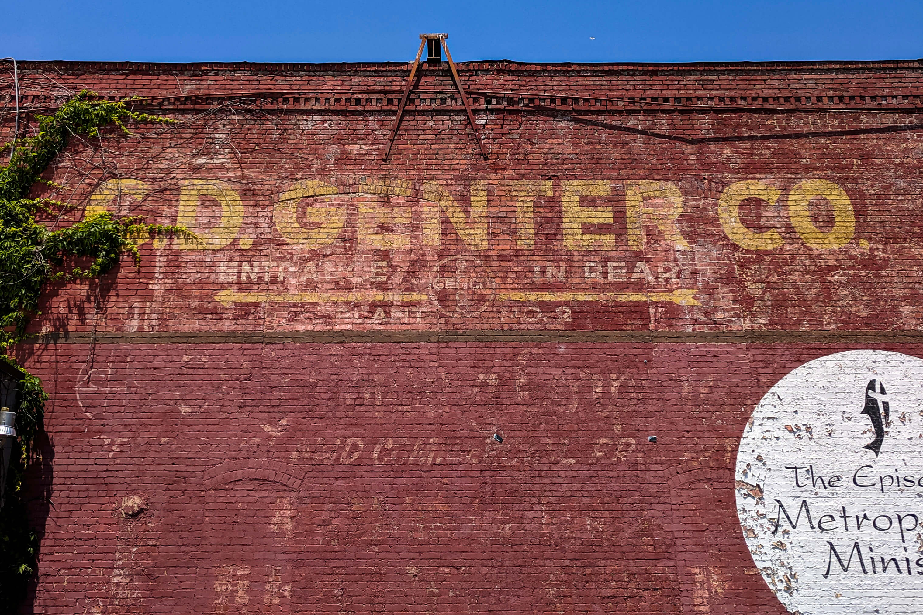 A very weathered C.D. Genter Co. logo painted onto a brick building