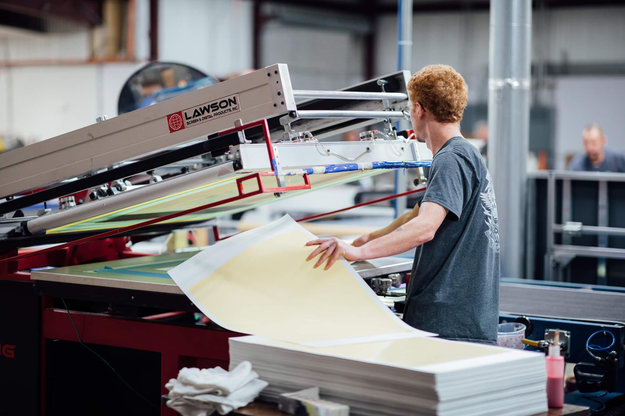 Medium shot of a man screen printing vinyl decals. Photo was taken for the Go Decals website redesign.