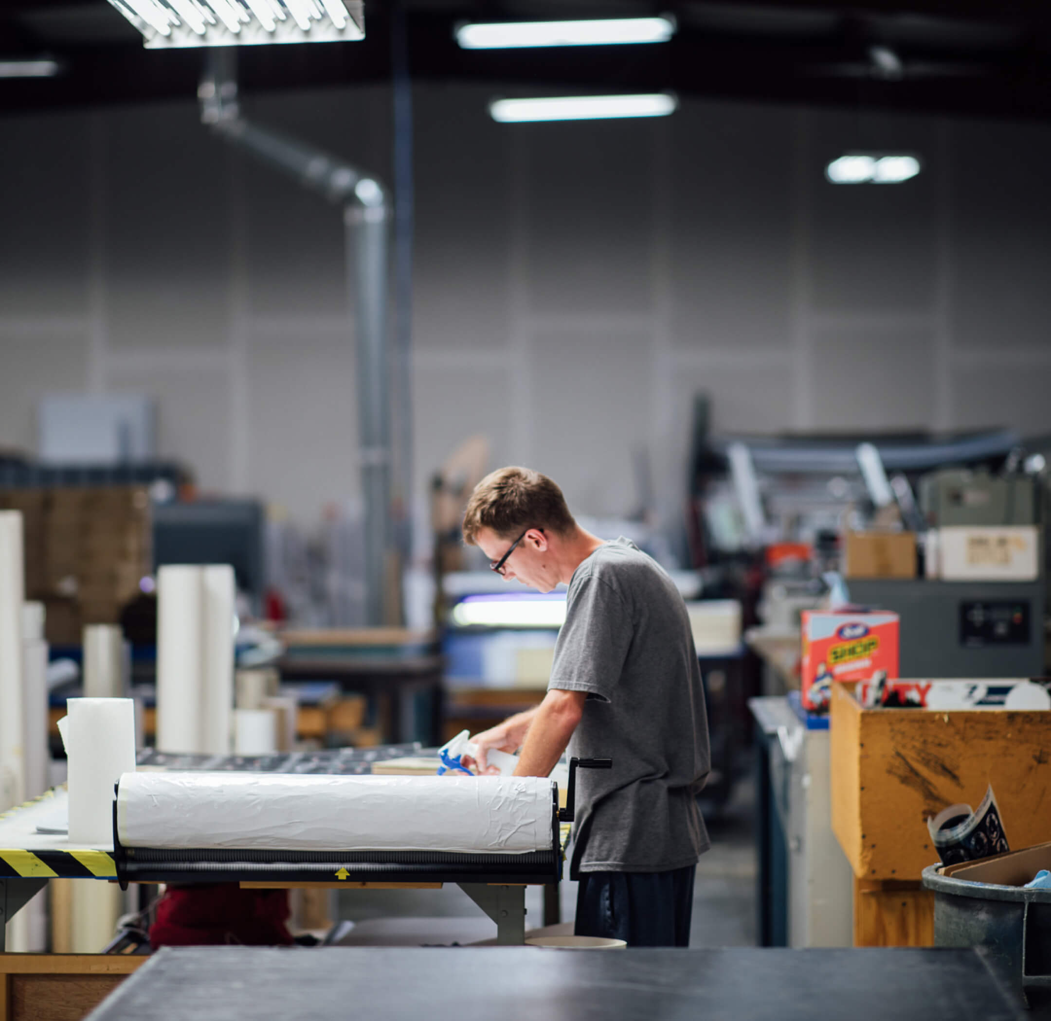 Long shot of a man working in the Go Decals facility.