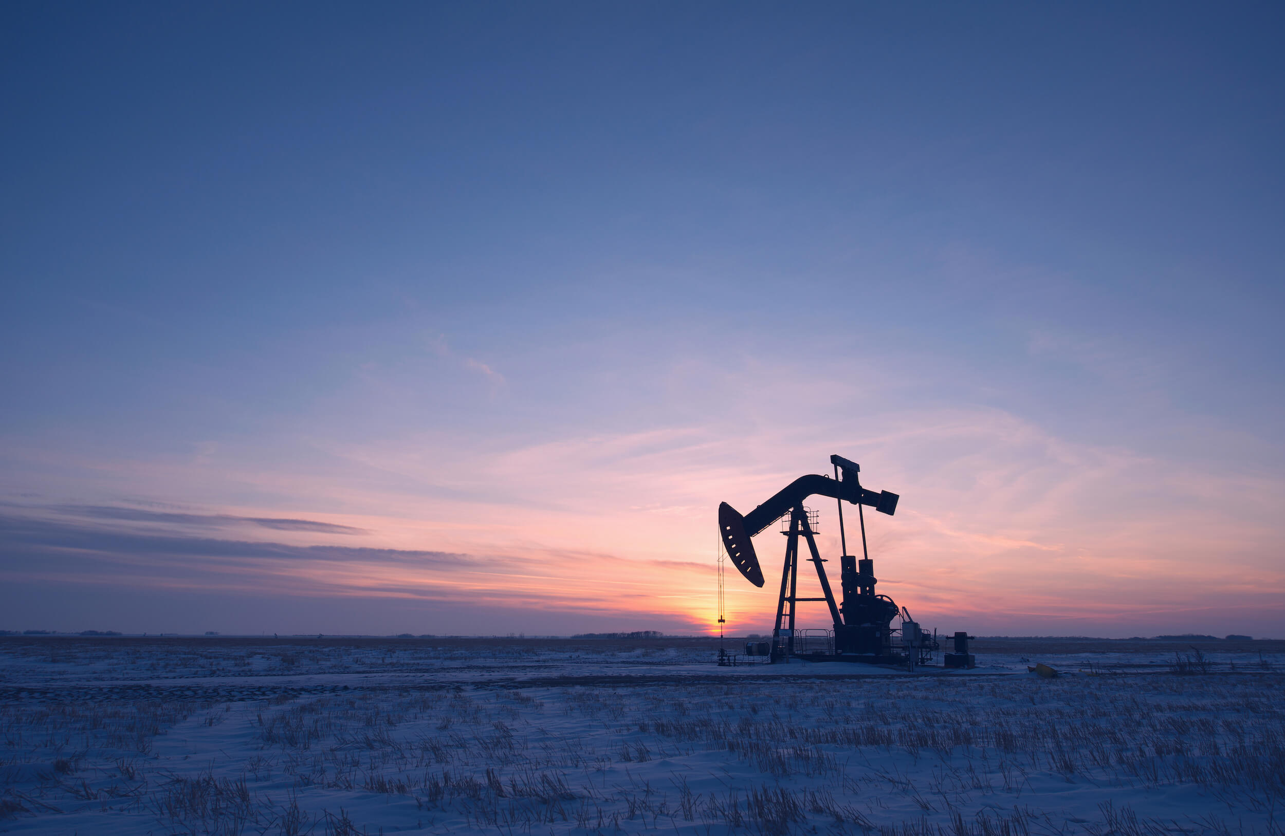 Landscape photo of an oil pump jack at dusk