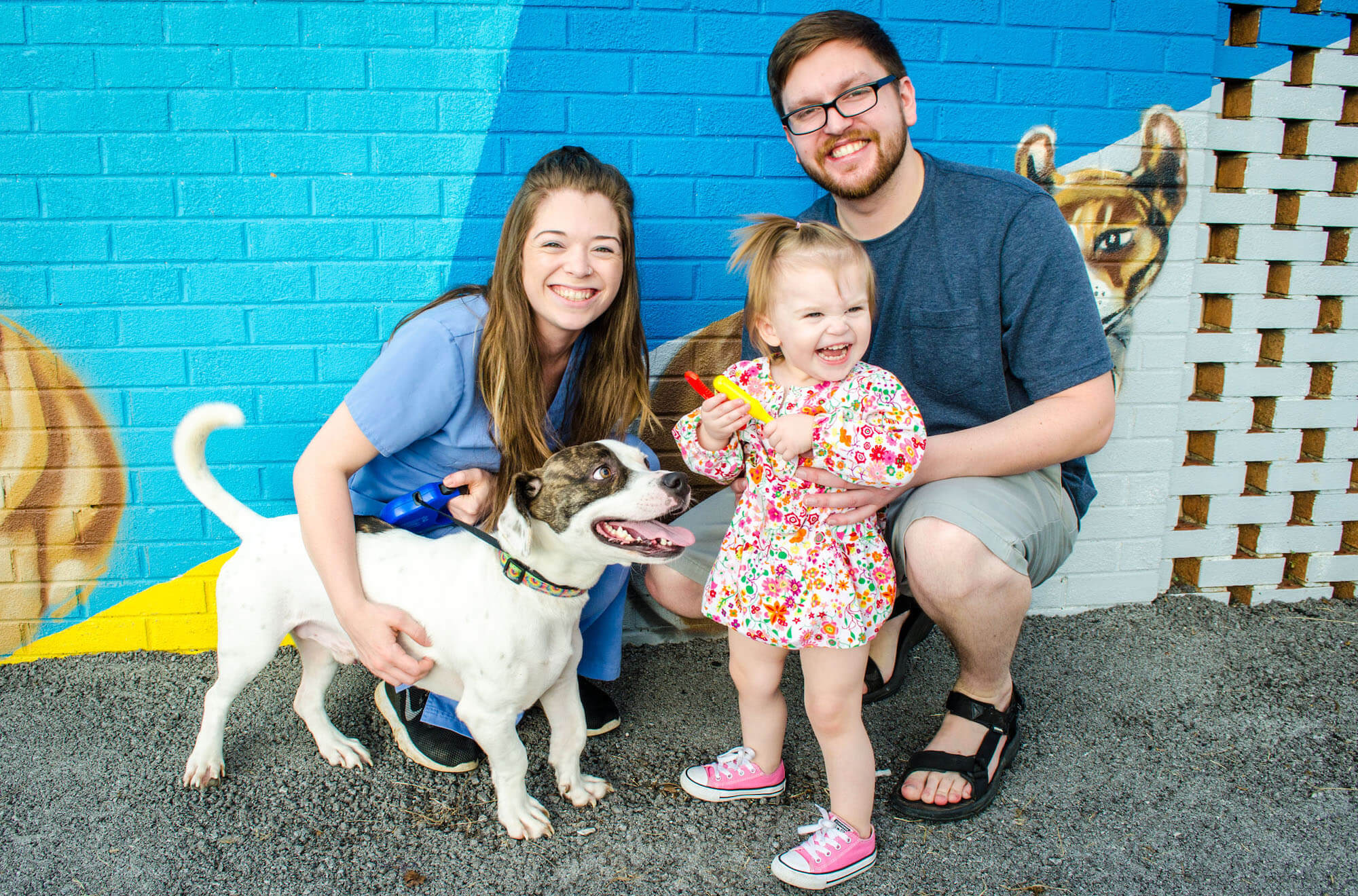 Leigh Ann, a maker volunteer, took beautiful photos of the Chattaneuter staff. Pictured are a couple with their daughter and dog standing in front of the Chattaneuter mural.
