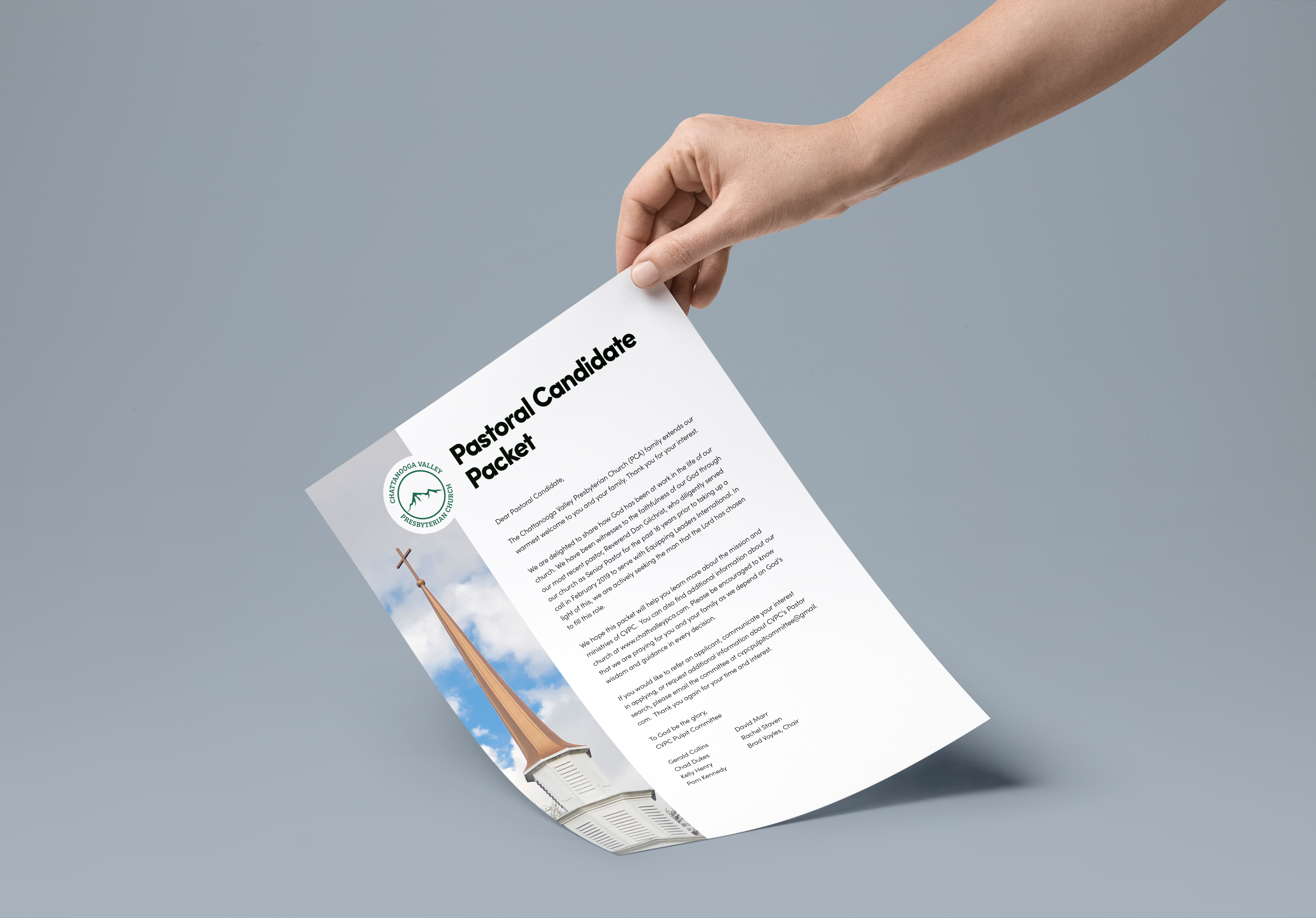 Hand holding front page of a candidate packet for a church. The sheet of paper being held includes a picture of the church, church logo, and welcome letter from hiring committee.