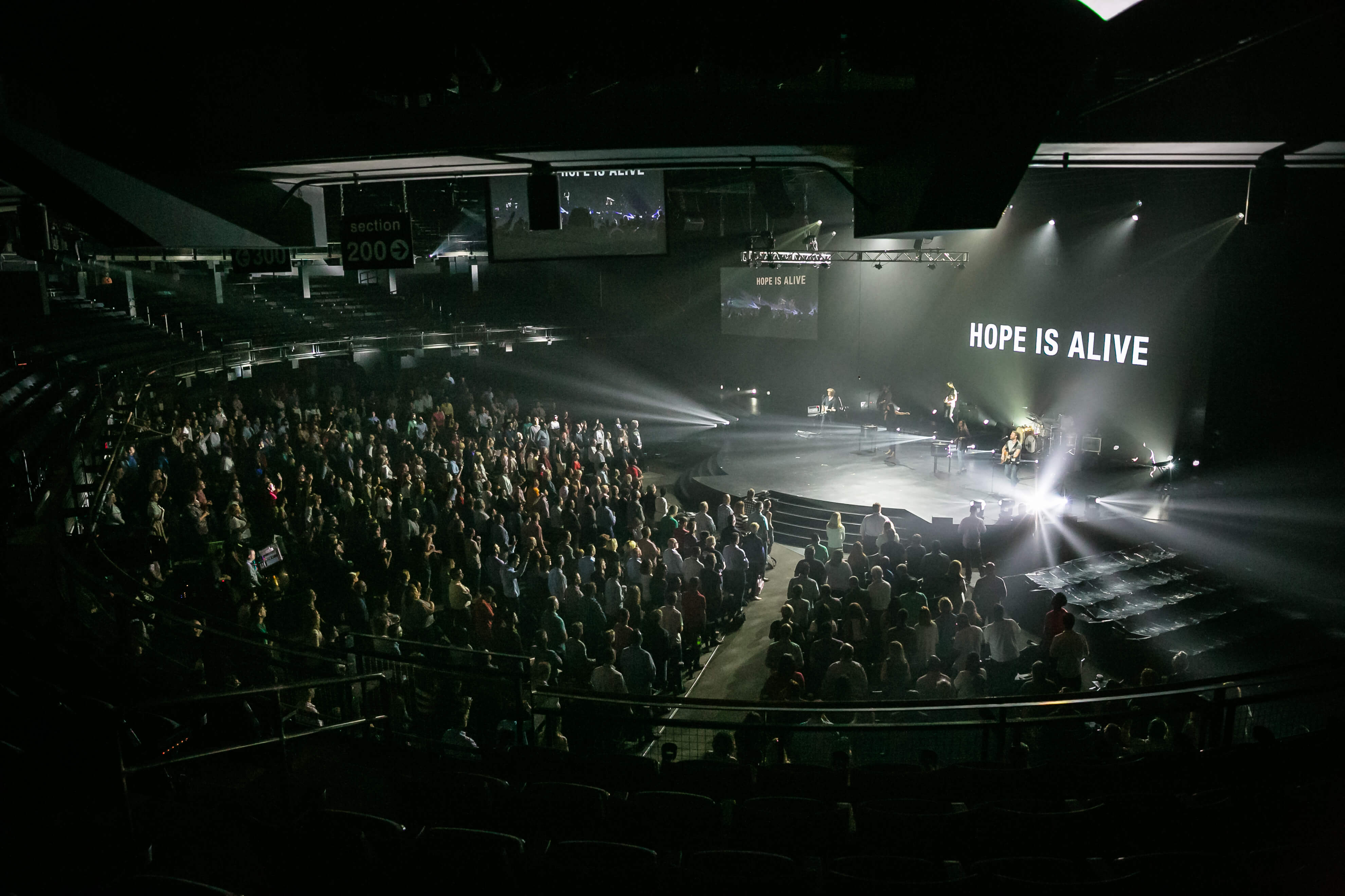 "At a concert venue, a crowd stands and signs along with a band. A large screen reads ""Hope is Alive""."