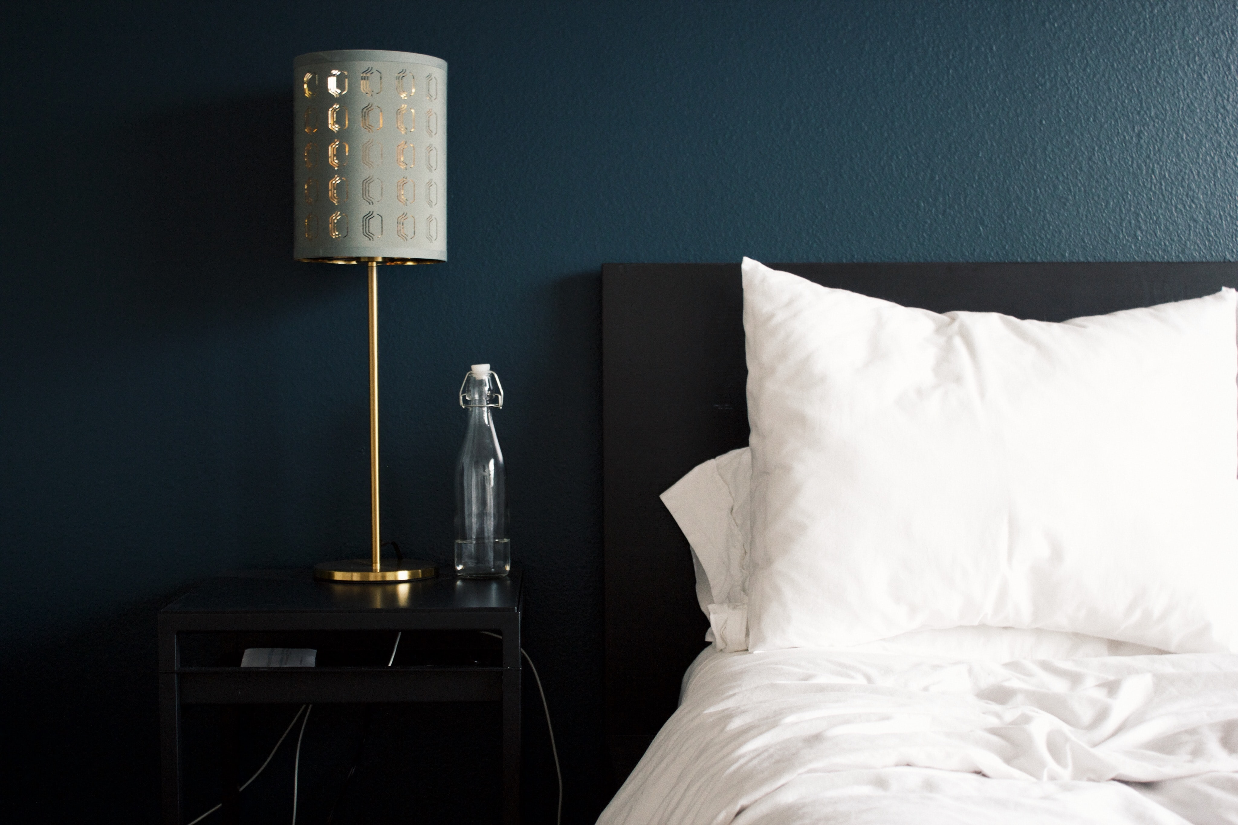 A photo of a hotel room bed and bedside table with a lamp on it