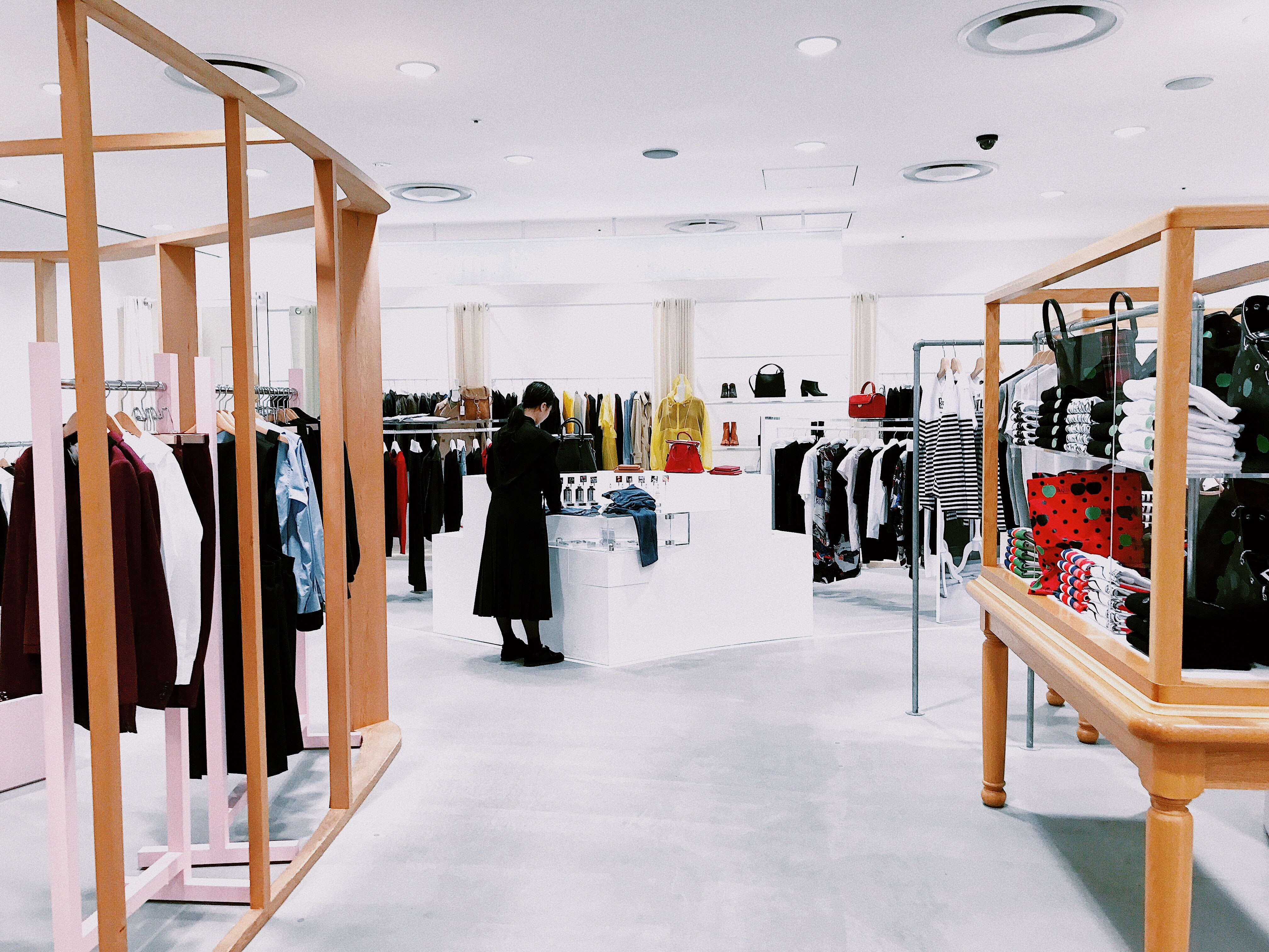 A picture of a clothing store with wide, light spaces, some clothing racks on the side and a person in the background at a counter