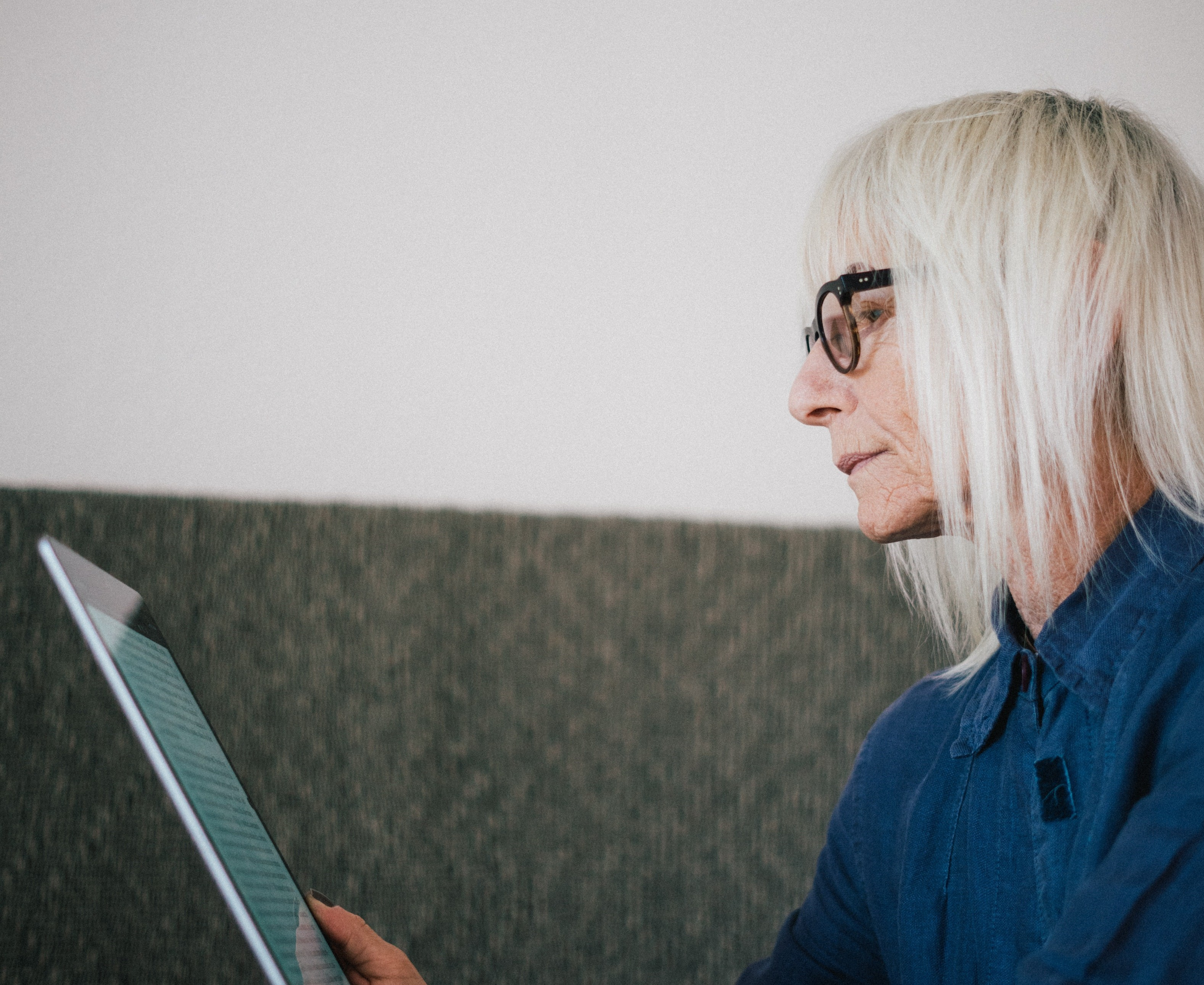 A woman with glasses and white hair looks at a tablet screen.