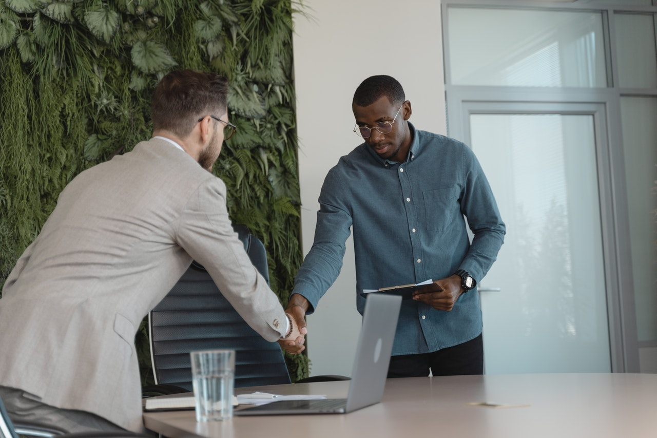 Two young men shake hands across a table. There's an office chair, a laptop and a glass of water so it looks as if they have just finished a meeting.