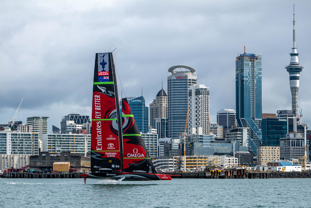 A racing yacht with red sails and sponsorship logos, in front of the Auckland skyline.