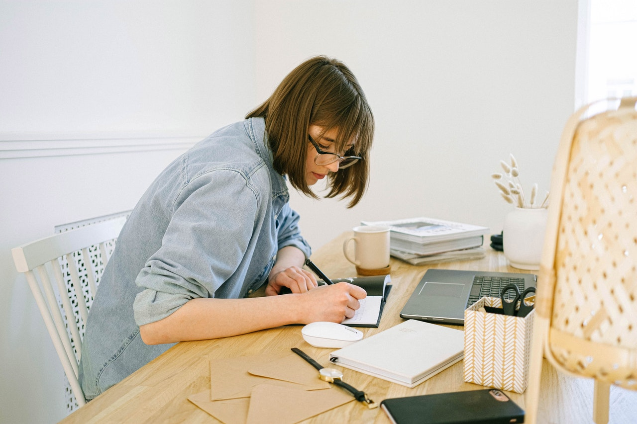 A young woman in a pale blue denim shirt with the sleeves rolled up sits at a table, writing in a notebook. She is surrounded by work items including a laptop, watch and coffee mug.