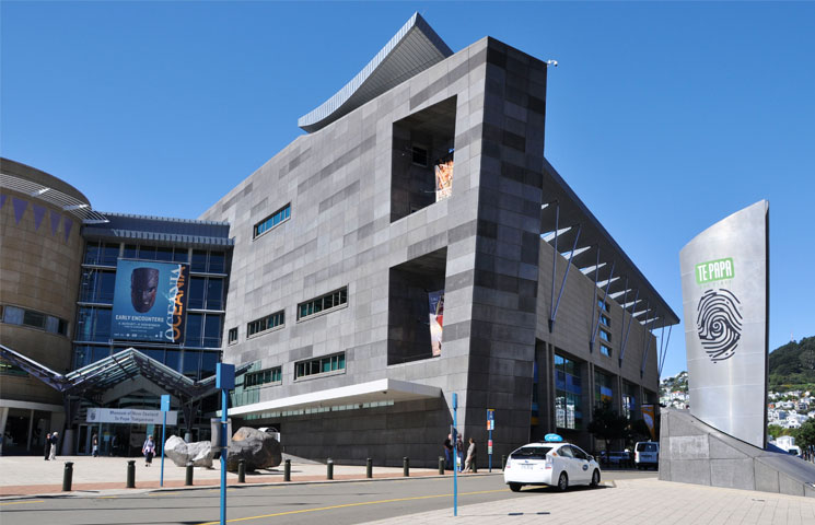 Exterior photo of the Te Papa Museum, an angular modern building with a blue sky in the background. You can see there is level access to the main entrance.