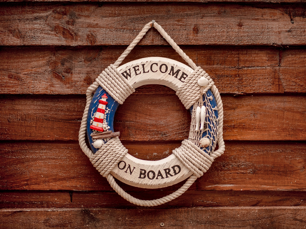 "A wooden sign hanging on a wall, designed like a lifebuoy ring, with the words ""Welcome on board""."