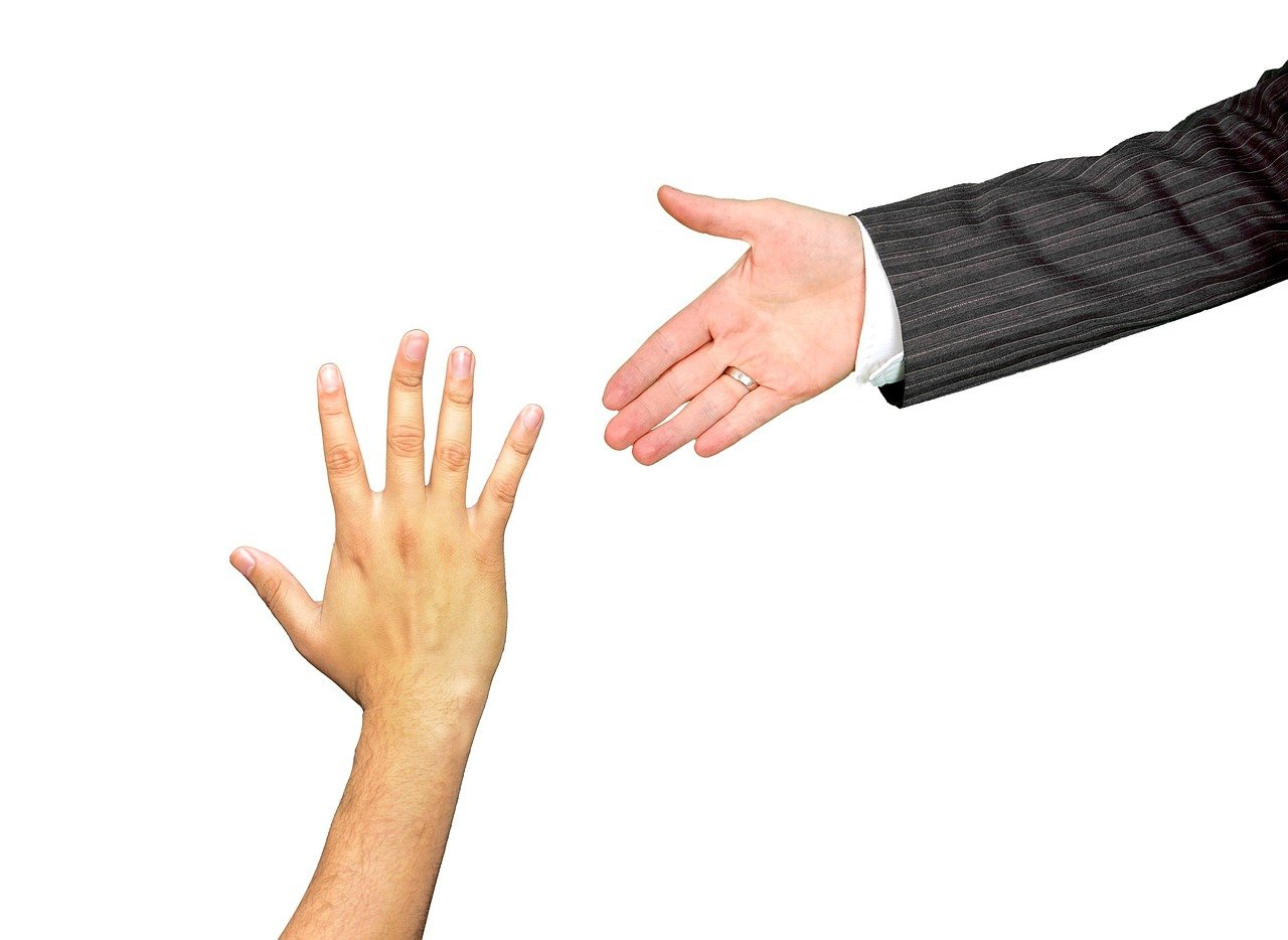 A man's arm wearing a business jacket, reaching out to what looks like a younger man's hand, which is reaching up.