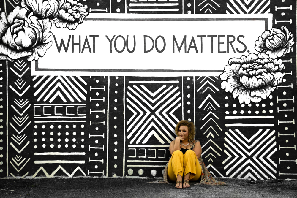 """Young woman in yellow trousers, sitting on the street in front of a poster saying """"What you do matters""""."""