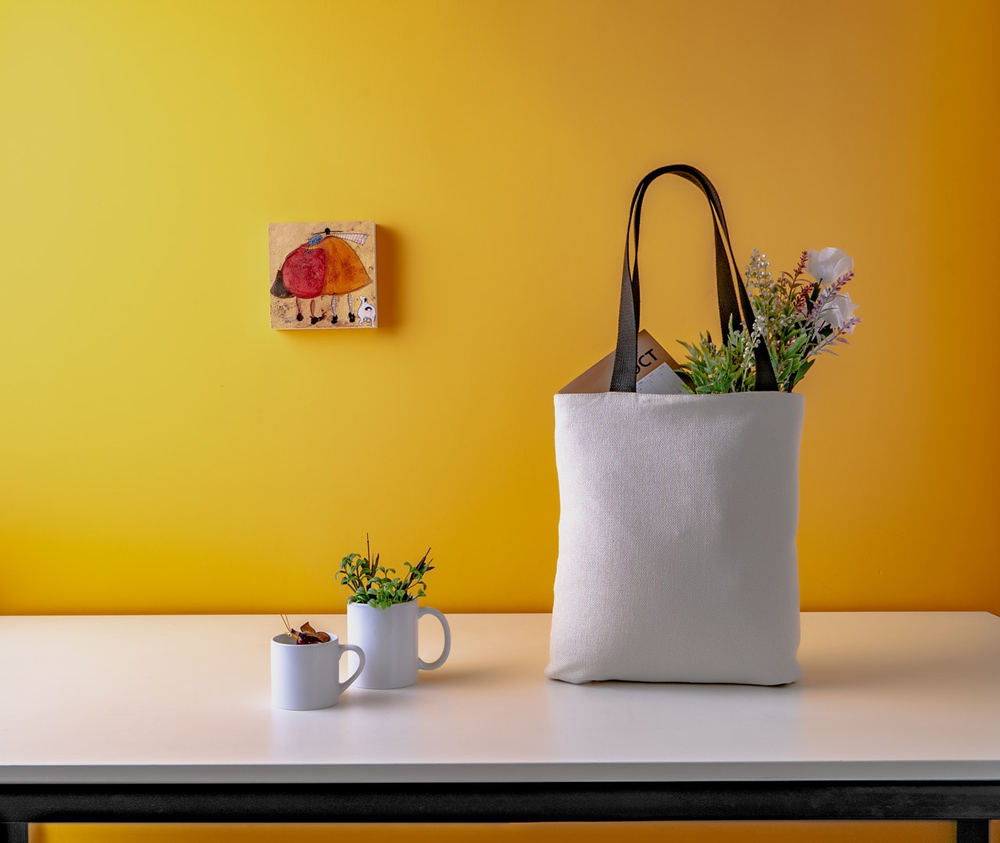 A white shopping bag on a kitchen counter, with a yellow wall behind it.