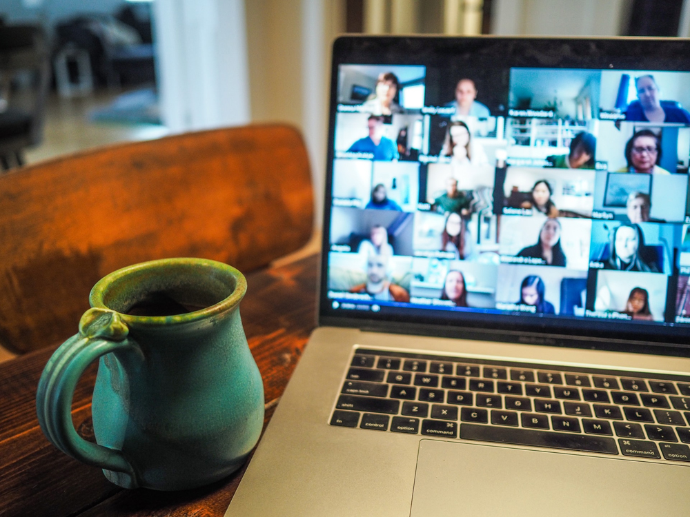 A laptop on a table, showing a screen with many faces taking part in an online meeting. Next to it, a coffee cup.