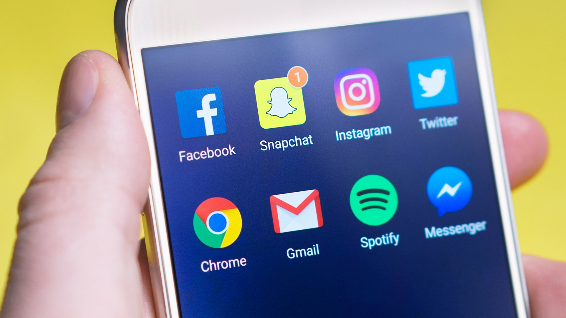 Yellow background. Close up of a hand holding a phone with the Facebook, Snapchat, Instagram, Twitter, Chrome, Gmail, Spotify and Messenger Apps.