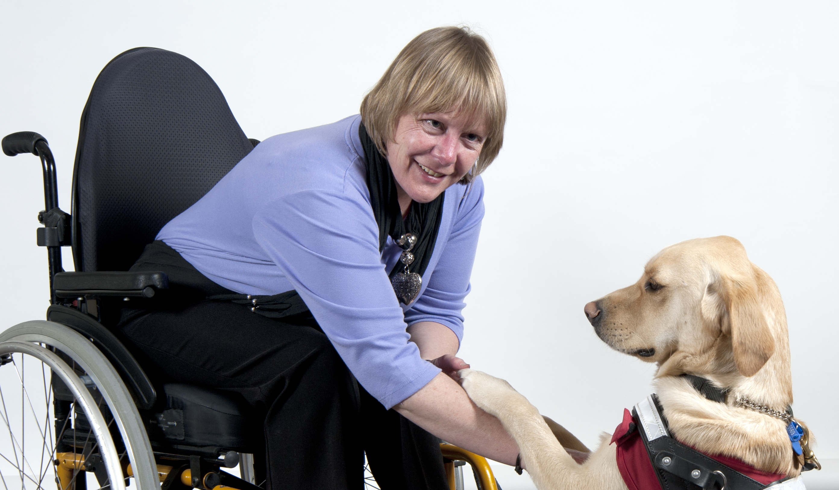 A woman is sitting in a wheelchair smiling at the camera. She has light brow hair and is wearing a blue top and large heart pendant. She is leaning forward and shaking hands with her guide dog.