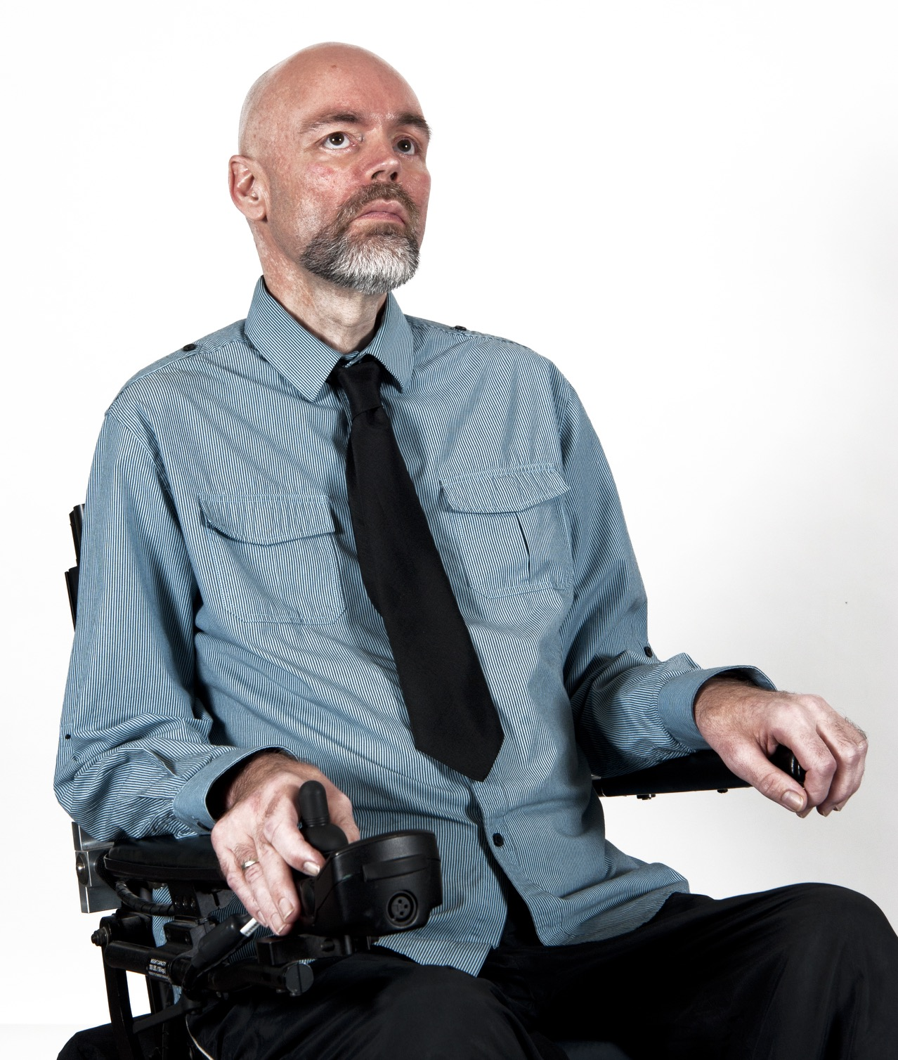 A man wearing a blue shirt and black tie is sitting in a power chair. He is looking off camera.
