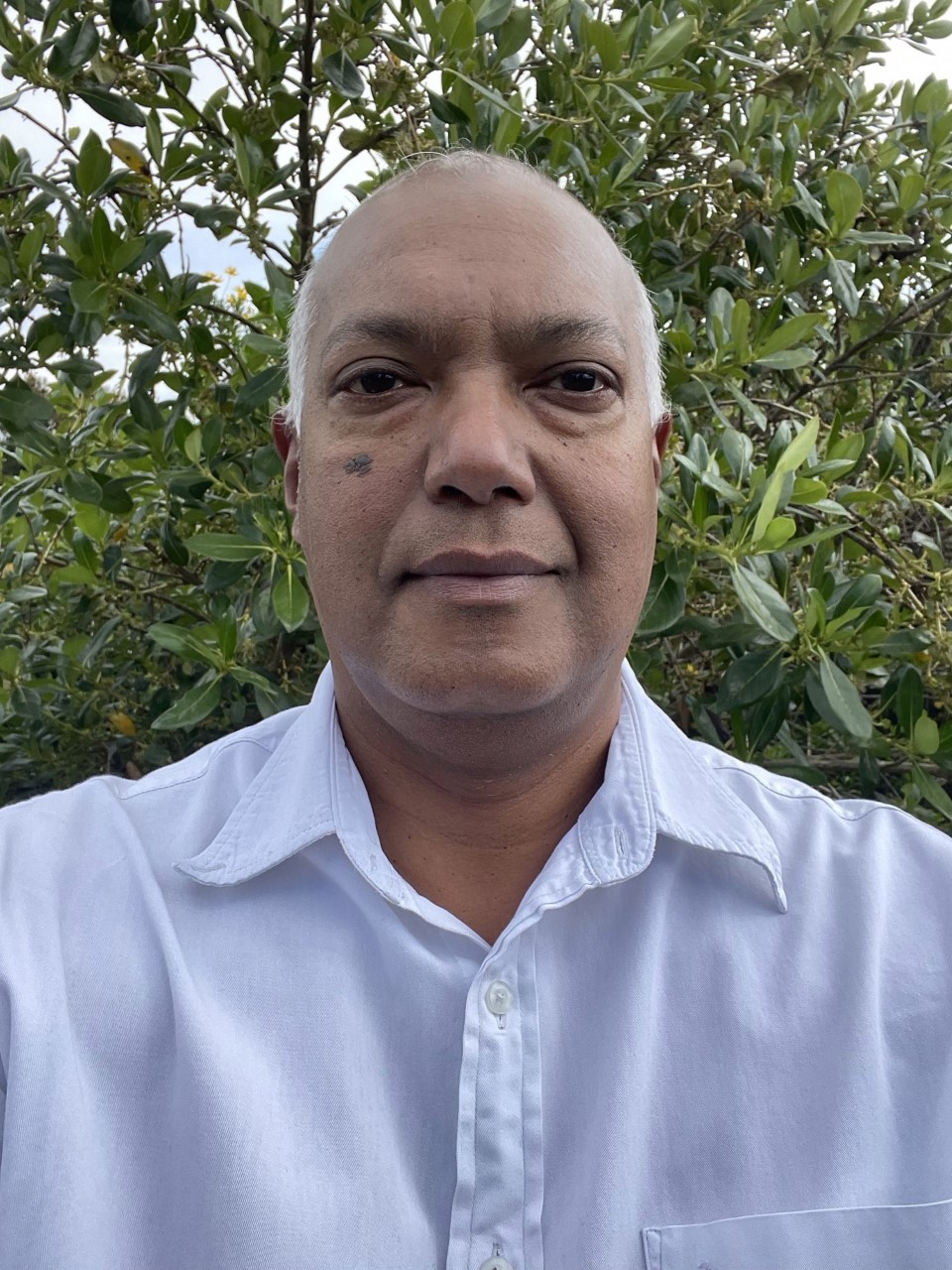A man with dark skin, dark eyes and grey hair is standing in a garden. He is wearing a black white shirt. In the background are trees and blue sky with clouds.