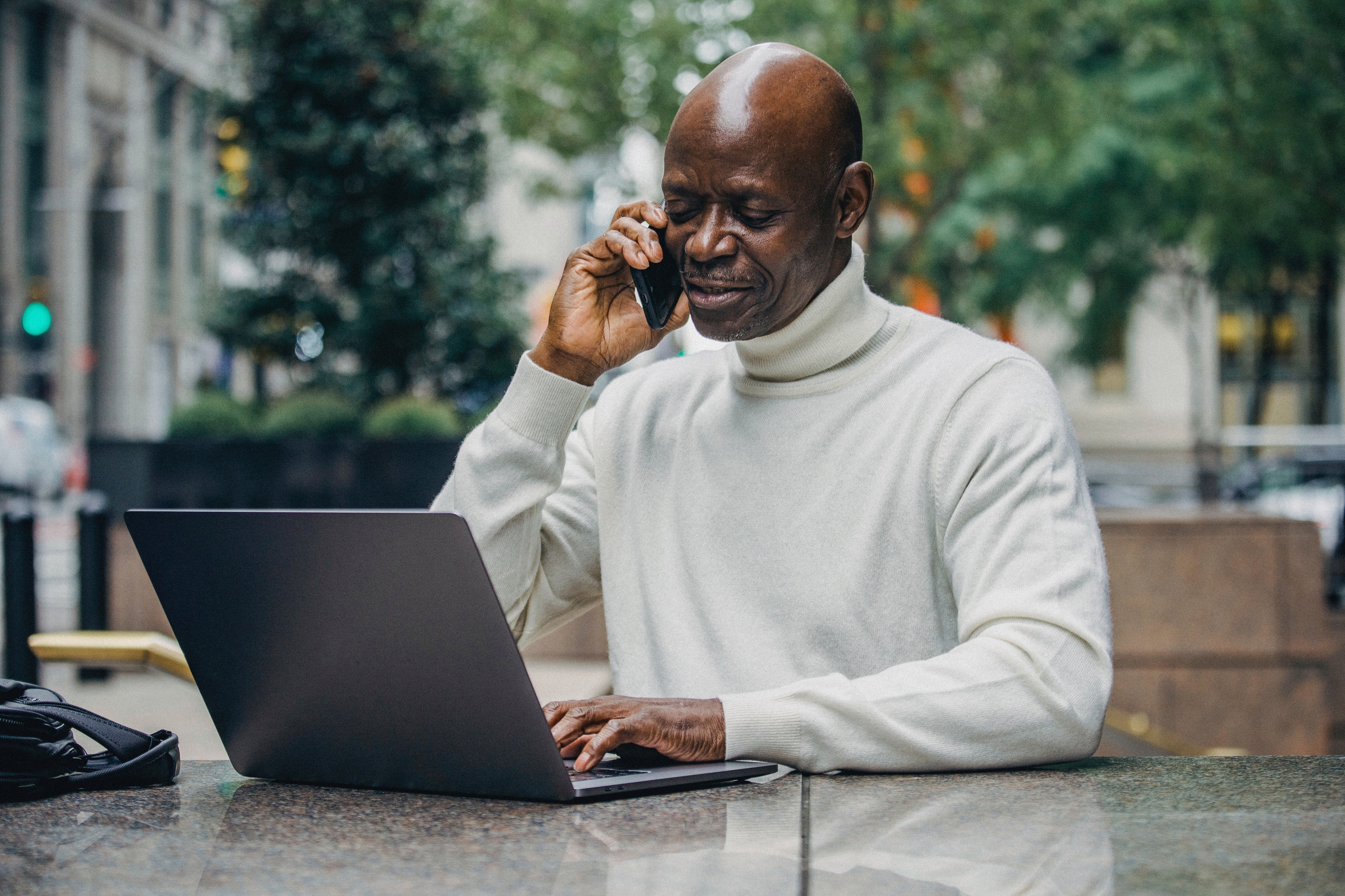 An older man with dark skin and a moustache is talking on a phone. He is sitting at an outdoor table looking at his laptop in a city square. There are buildings, people and trees in the background.