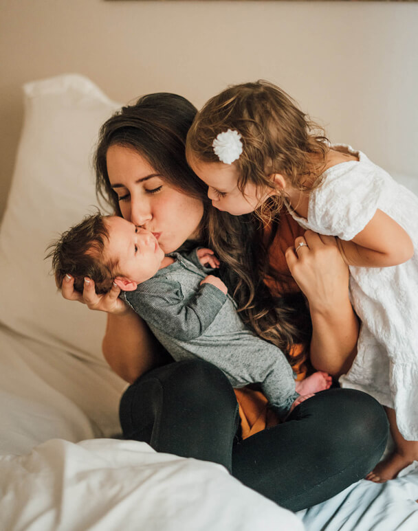 Mom kissing kids