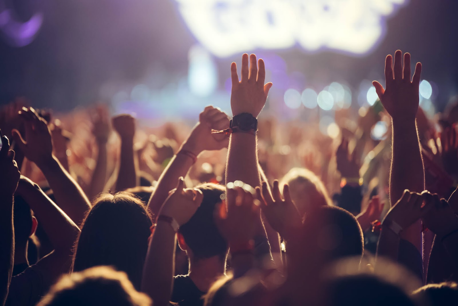 A crowd with their hands raised at a concert