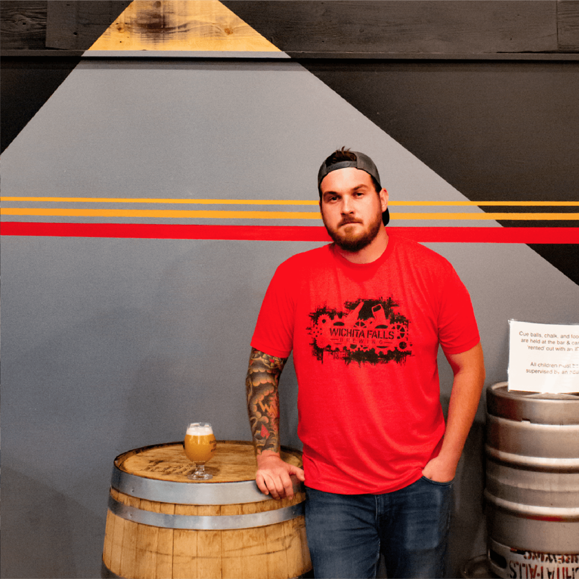 Jorden, our Head Brewer, stands in a red shirt by the inside mural with the red stripes, lookin real cool, posing with his beer