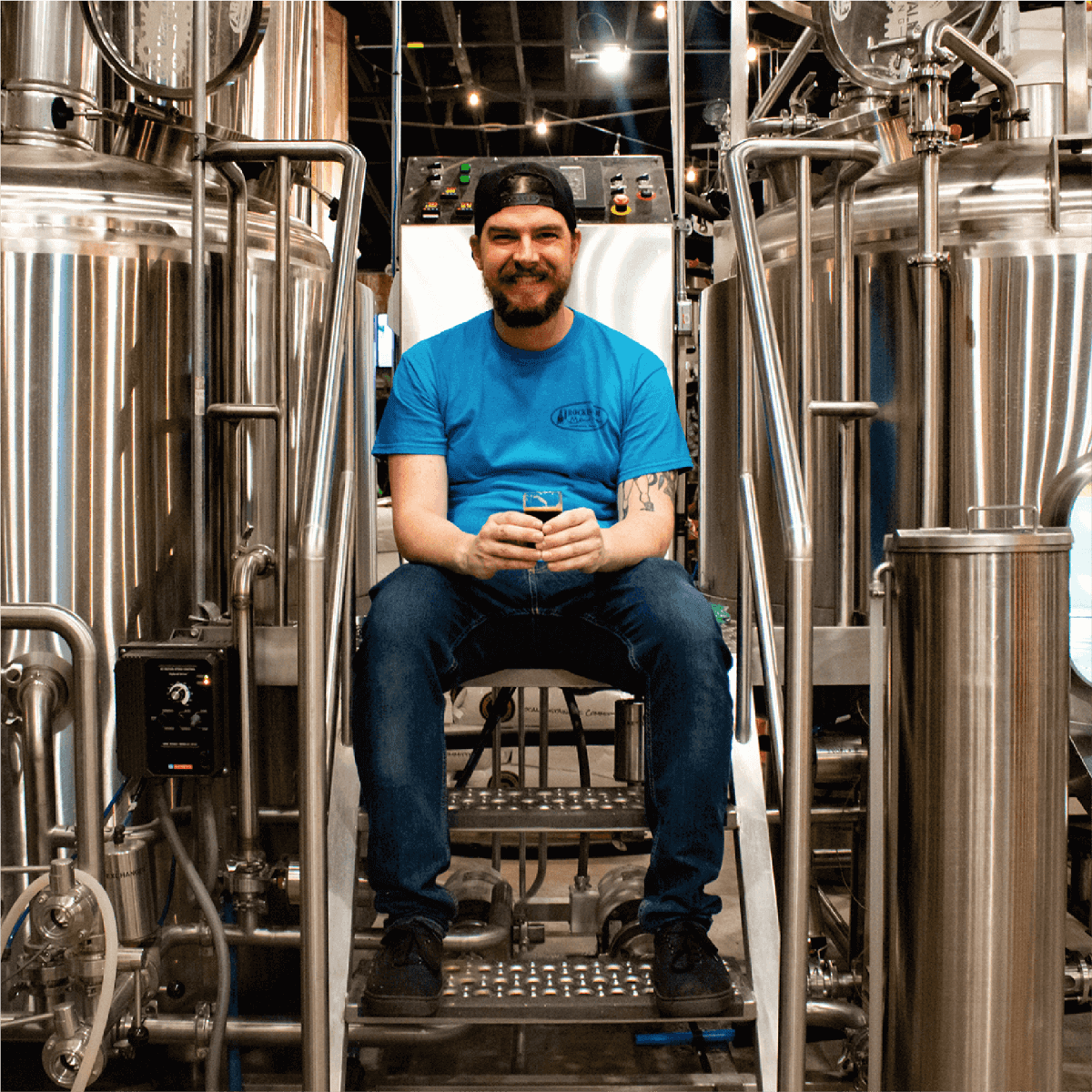 Eric, our Beer-tender sitting between two tanks with a huge grin on his face