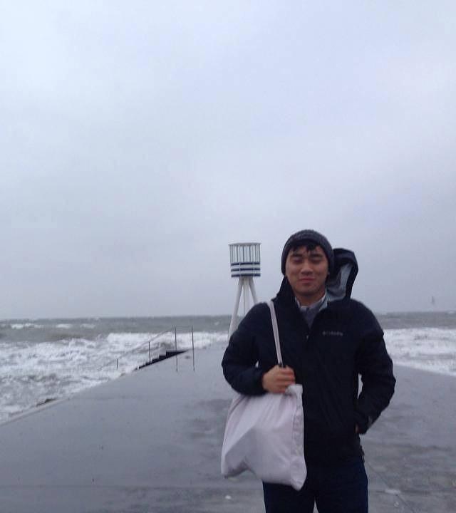 Jonathan standing on a windy concrete pier in Denmark.
