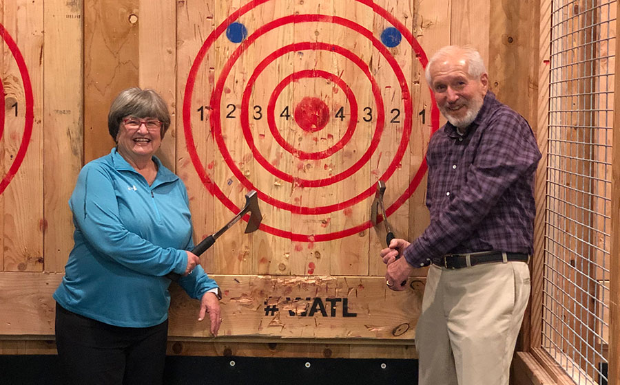 An older couple retrieve their axes from the target.