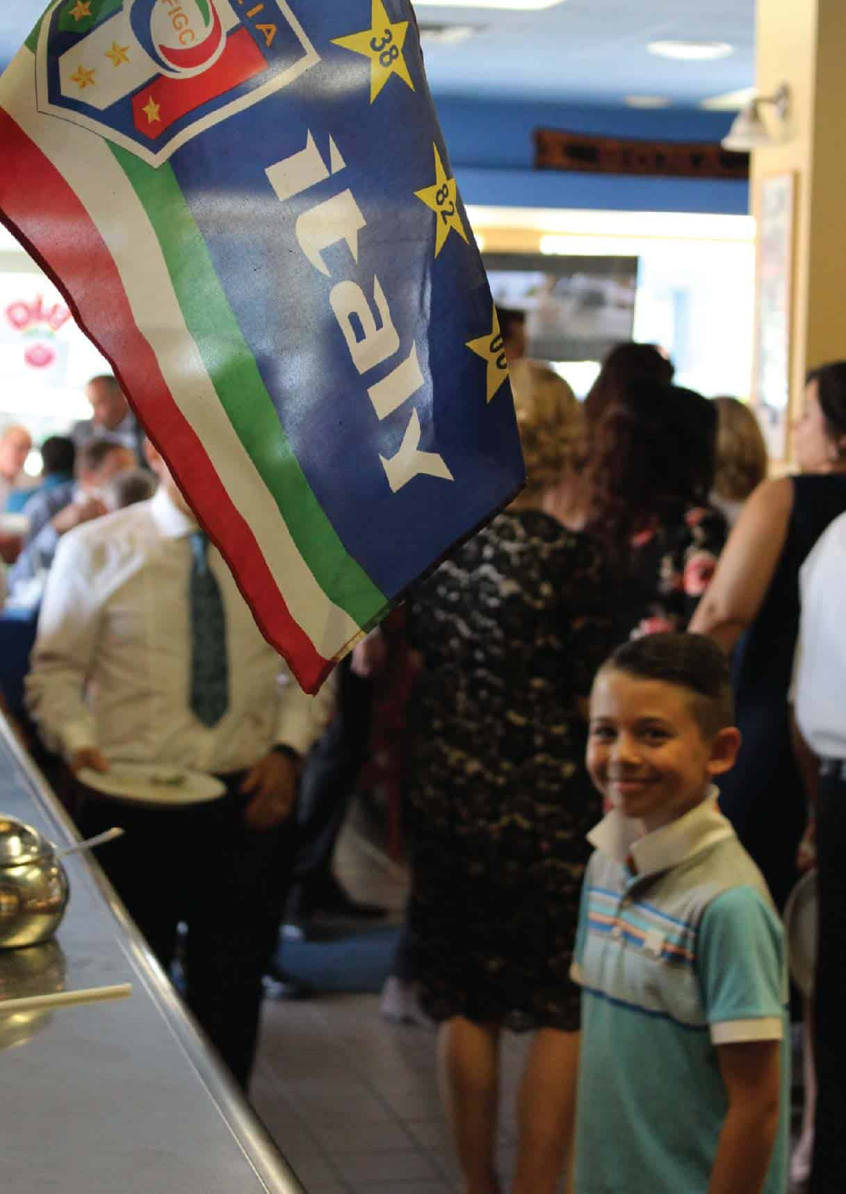 YOUNG BOY SMILING BESIDE THE ITALIAN FLAG