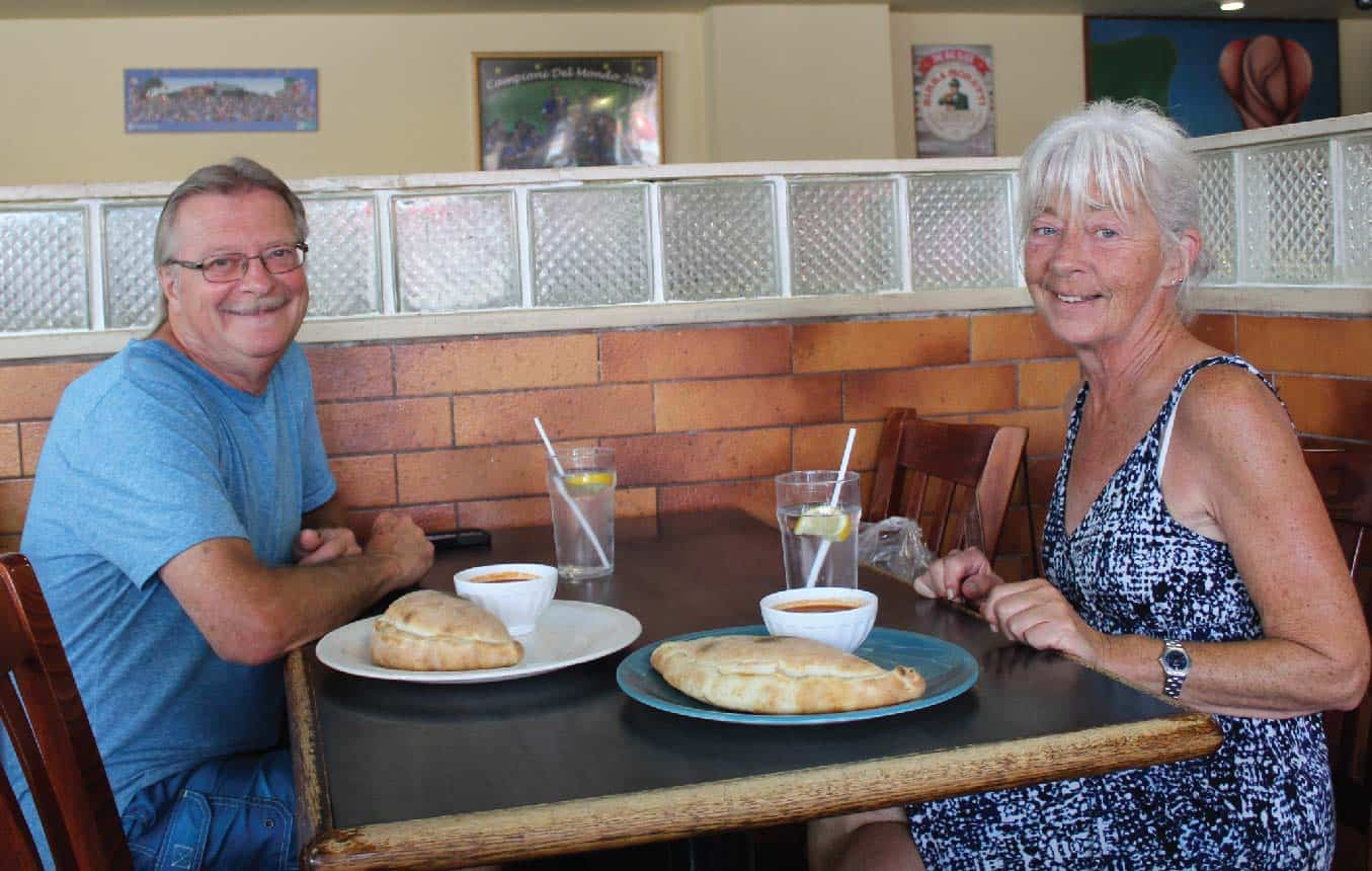 HAPPY ELDERLY COUPLE ENJOYING PANZEROTTI